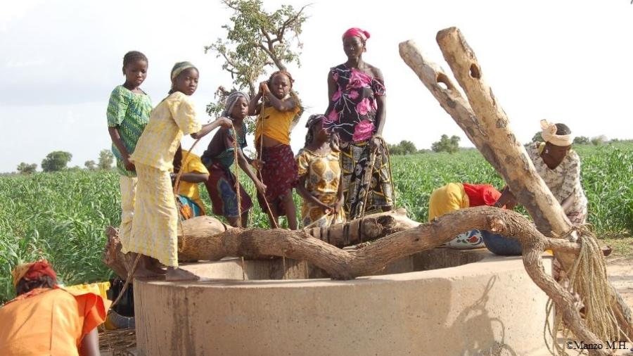 Des jeunes filles et femmes entrain de puisées de l'eau dans un puits